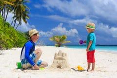 A construção do pai e do filho fortifica na praia da areia Fotos de Stock Royalty Free