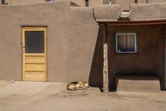 Construção do povoado indígeno do adôbe da lama no sudoeste americano com outisde adormecido de madeira novo da porta e do cão -  fotos de stock