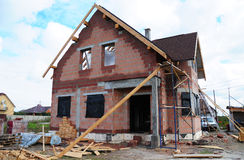 Construção do telhado e casa cerâmica nova dos tijolos da construção com a chaminé, as claraboias, o sótão, a fachada modular e o fotografia de stock royalty free