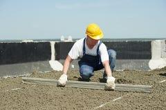 Construção do telhado roofer do trabalhador que nivela com alaúde do flutuador fotografia de stock