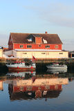 Construção e barcos vermelhos de Henningsvaer   espelhar imagem de stock royalty free