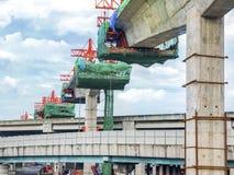 Construção em uma ponte do trilho de alta velocidade com cargos no meio do guindaste imagem de stock