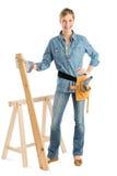 Construção fêmea com mão na prancha guardando anca da madeira foto de stock royalty free