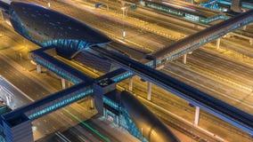 Construção futurista da estação do metro e do bonde de Dubai e arranha-céus luxuosos atrás do timelapse da noite filme
