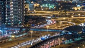 Construção futurista da estação do metro e do bonde de Dubai e arranha-céus luxuosos atrás do timelapse da noite video estoque