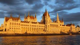 A construção húngara do parlamento no banco do Danube River exposto aos raios do sol do grupo do sol com o céu nebuloso no fotografia de stock royalty free