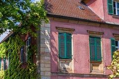Construção histórica com janelas da estrutura e os obturadores verdes imagem de stock royalty free