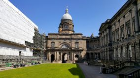 Construção histórica com o céu azul do gramado e do espaço livre no fundo fotografia de stock