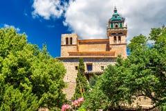 Construção histórica do monastério de Valdemossa e árvores e plantas do verde vívido imagem de stock