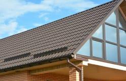 A construção moderna da casa com telhado do metal, o sistema da calha da chuva e a proteção do telhado da neve embarcam, nevam pr Imagens de Stock