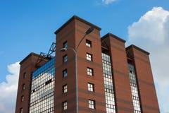 Construção moderna do tijolo e do vidro em um fundo do céu azul com nuvens fotografia de stock royalty free