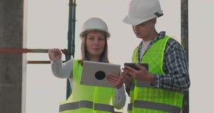 Construção na construção com um fêmea e coordenadores masculinos que usam uma tabuleta e um telefone celular para visualizar a co vídeos de arquivo