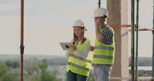 Construção na construção com um fêmea e coordenadores masculinos que usam uma tabuleta e um telefone celular para visualizar a co video estoque