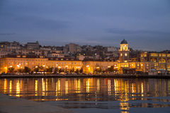Construção na noite na costa adriático com reflexão na água, Trieste, Itália Imagens de Stock