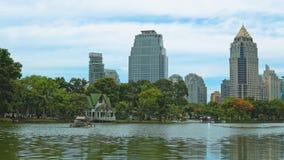 Construção no distrito financeiro da cidade que negligencia o parque e o lago verdes Estilo urbano Colagem moderna dos edifícios vídeos de arquivo