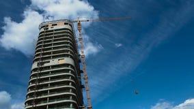 Construção residencial inacabado sob o céu azul e as nuvens, trabalho do guindaste de construção, espaço da cópia filme