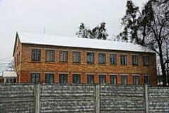 Construção residencial na neve com uma cerca de pedra imagem de stock