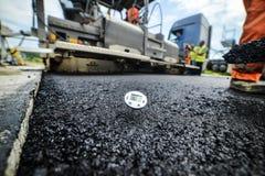 Construção rodoviária resistente Asfalto quente que estão sendo colocados e FO medidas Imagem de Stock Royalty Free