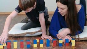 Construção torres dos blocos e dos cubos A mamã e o filho que jogam junto com o brinquedo colorido de madeira da educação obstrue video estoque