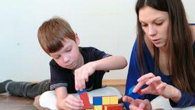 Construção torres dos blocos e dos cubos A mamã e o filho que jogam junto com o brinquedo colorido de madeira da educação obstrue vídeos de arquivo