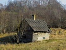 A construção velha de um bathhouse alastrando em um campo em uma exploração agrícola em Letónia fotografia de stock