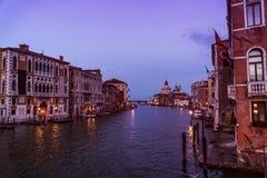 Construção Venetian no tempo do por do sol com luzes da iluminação, barcos e o céu surpreendente sobre o canal grande Foto de Stock
