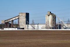 Construções agrícolas no fundo de um campo arado e de um céu azul Foto de Stock