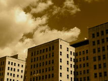 Construções altas contra um céu nebuloso no Sepia Fotos de Stock Royalty Free