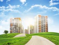 Construções altas, montes verdes e estrada contra o céu Fotografia de Stock Royalty Free