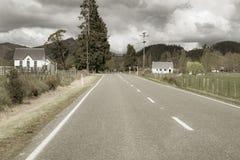 Construções brancas um cada lado da estrada reta que passa no meio foto de stock royalty free