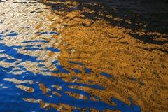 Construções da reflexão, iluminadas pelo sol, na água Imagens de Stock