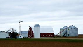 Construções de exploração agrícola com moinho de vento ativo em um dia nebuloso em Minnesota video estoque