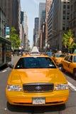 Construções de Manhattan e táxis que conduzem em um dia ensolarado, New York City, EUA Imagem de Stock
