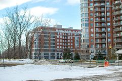 Construções modernas do condomínio com janelas e balcões enormes e neve suja imagens de stock