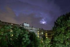 Constru??es e ?rvores verdes na noite, c?u iluminado durante uma tempestade do rel?mpago imagens de stock royalty free