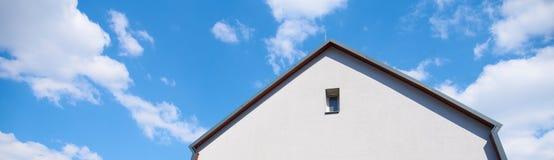 Constru??o, casa de campo, contra um c?u azul com nuvens brancas foto de stock royalty free