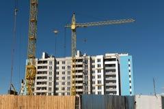Construcción con la grúa en fondo del cielo azul imagen de archivo