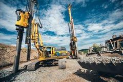 Construcción de la carretera con maquinaria resistente Dos funcionamientos rotatorios de los taladros, de la niveladora y del exc Fotos de archivo libres de regalías