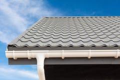 Construcción de la casa del panel del SORBO Nuevo tejado de teja gris del metal con el canal blanco de la lluvia imagen de archivo libre de regalías