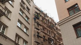 Construcción de la reparación del concepto del andamio los trabajadores reparan a la fachada del edificio los trabajadores repara almacen de video
