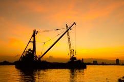 Construcción de la silueta en un río en puesta del sol Foto de archivo libre de regalías