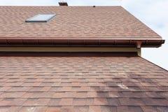 Construcción de la techumbre y casa del edificio nueva con la chimenea, los tragaluces, el ático, las ventanas abuhardilladas y l fotografía de archivo libre de regalías