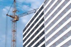 Construcción de un edificio de varios pisos Grúa de la casa y de construcción en fondo del cielo imágenes de archivo libres de regalías