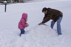 Construcción de un muñeco de nieve Foto de archivo libre de regalías