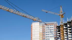 Construcción del edificios de varios pisos Dos grúas de construcción contra el cielo funcionan en el emplazamiento de la obra almacen de metraje de vídeo