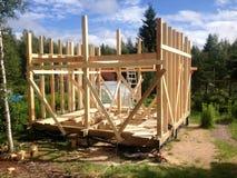 Construcción del marco de una casa de madera Etapa de la erección del bastidor de la pared La casa en los zancos Verano, construc imagen de archivo