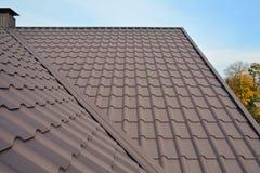 Construcción del tejado del metal contra el cielo azul Materiales de techumbre Tejado de la casa del metal Materiales de construc imagen de archivo