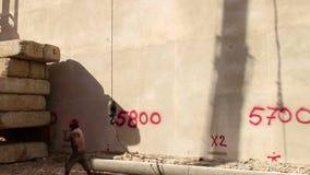 CONSTRUCCIÓN: El trabajador conecta el gancho y el cable con el bloque de cemento masivo almacen de metraje de vídeo