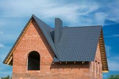 Construcción gris de la techumbre de la teja del metal y ladrillo Hous del edificio nuevo fotos de archivo libres de regalías