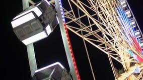 Construcción iluminada de Ferris Wheel que gira contra fondo oscuro del cielo nocturno almacen de metraje de vídeo